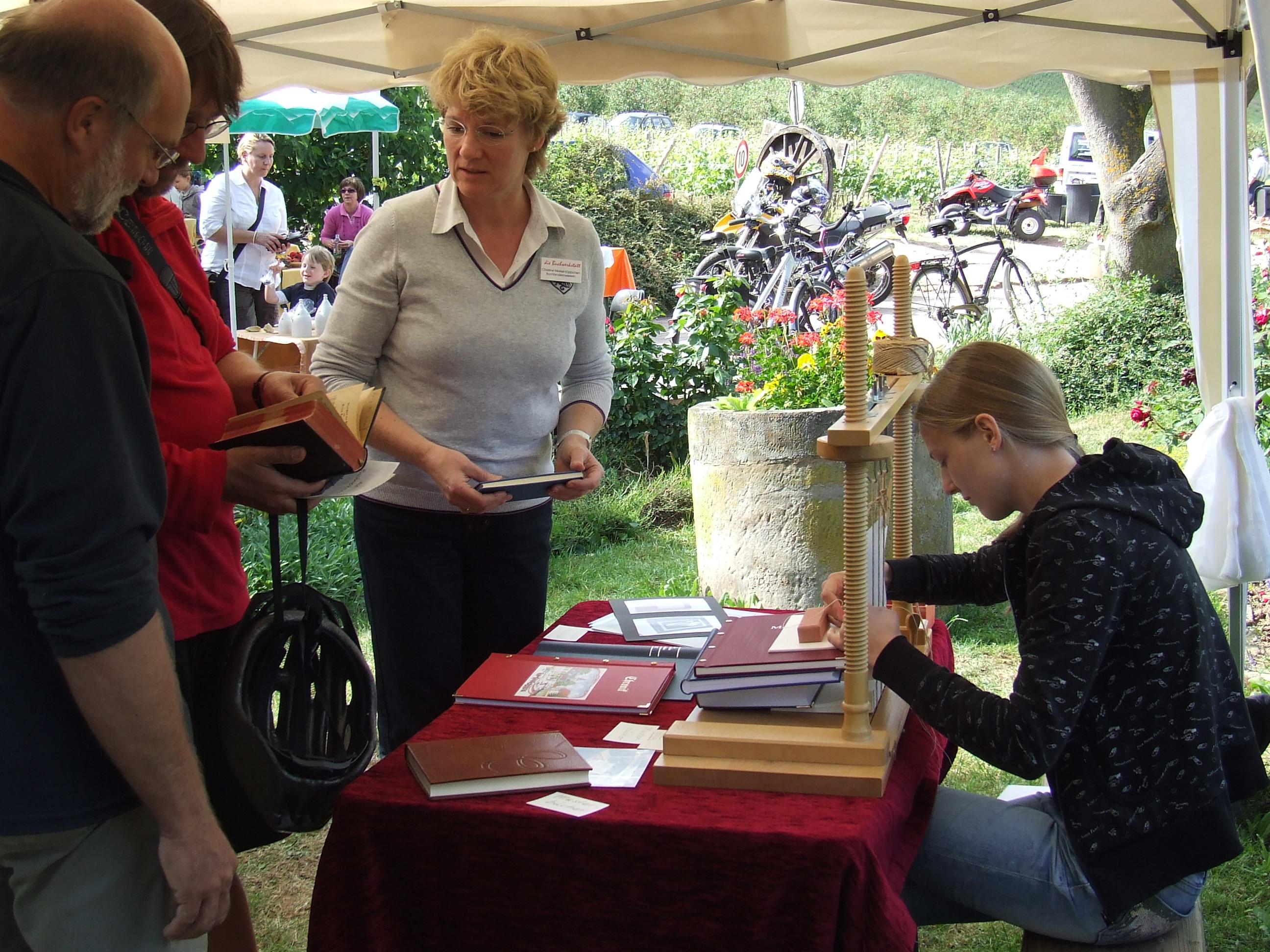 Buchwerkstatt: Beratungsgespräch während einer Ausstellung auf einem Handwerkermarkt